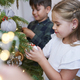 Sibling decorating Christmas tree together - PhotoDune Item for Sale
