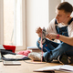 Young man using laptop and sewing machine while working on craft rug - PhotoDune Item for Sale