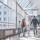 Full length of happy family with two little kids walking by airport terminal - PhotoDune Item for Sale