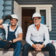 Builder adjusting har hat while sitting on porch with engineer - PhotoDune Item for Sale