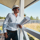 Housebuilder with drawings in arms leaning on porch railings - PhotoDune Item for Sale