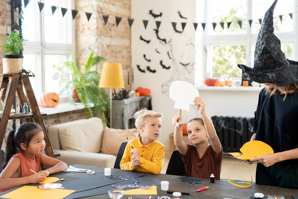 Little girl pointing at halloween paper symbol while showing it to cute boy - Stock Photo - Images