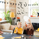 Little girl pointing at halloween paper symbol while showing it to cute boy - PhotoDune Item for Sale