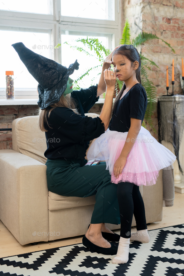 Young female in black witch attire applying makeup on eyes of little girl - Stock Photo - Images