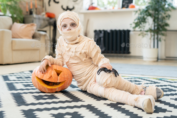Little boy mummy with spider and jack-o-lantern lying on the floor - Stock Photo - Images