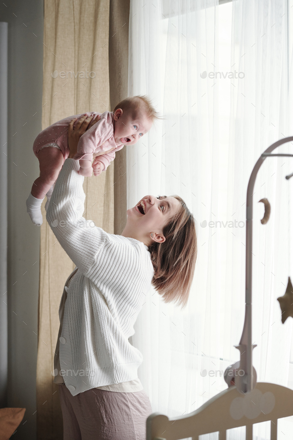 Cheerful young mother playing with her cute baby daughter - Stock Photo - Images