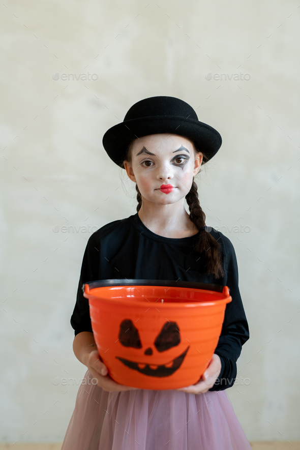 Girl with halloween makeup asking for treats while looking at you - Stock Photo - Images