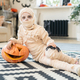 Little boy mummy with spider and jack-o-lantern lying on the floor - PhotoDune Item for Sale