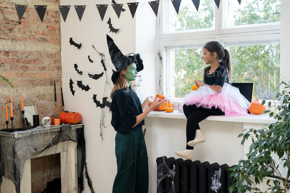 Young female in witch hat and little girl with pumpkins - Stock Photo - Images