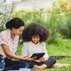 Cheerful young beautiful mother sitting with son with curly hair in park - PhotoDune Item for Sale