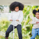 Two playful African sisters with curly hair enjoying and playing while riding scooter - PhotoDune Item for Sale