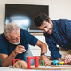 Playful senior father and young son sitting and relaxing on sofa at home playing video games - PhotoDune Item for Sale