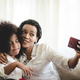 Cheerful young mother taking a selfie using smartphone with sister with curly hair - PhotoDune Item for Sale