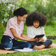Cheerful young beautiful mother sitting with kid with curly hair using digital tablet to studying - PhotoDune Item for Sale