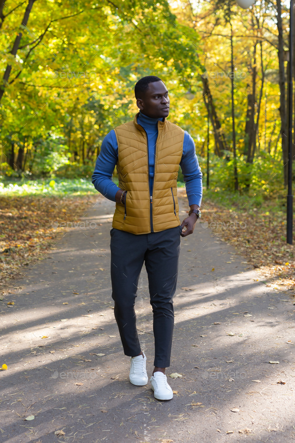 Cheerful african american young man in stylish clothes walks in autumn park on sunny warm autumn day - Stock Photo - Images