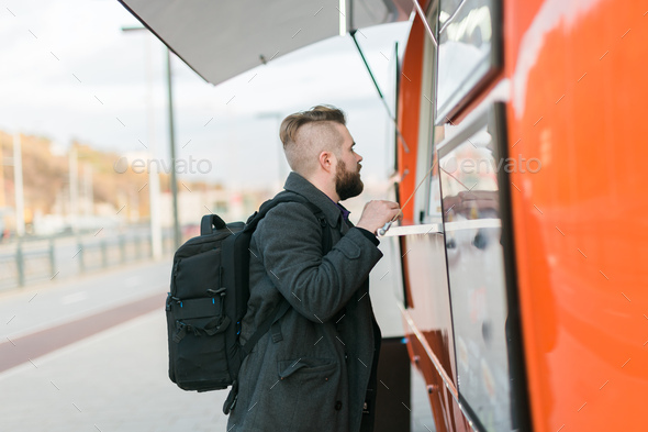 Portrait of man choosing fast food in food truck in the street. Meal, food industry and streetfood - Stock Photo - Images