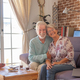 Smiling senior couple at home sitting on sofa looking at camera. Brick wall on background - PhotoDune Item for Sale