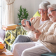 Smiling senior couple using phone in video call relaxing at home on the sofa - PhotoDune Item for Sale