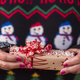 Woman in Christmas sweater holding and offering a surprise gift in a recycled paper - PhotoDune Item for Sale