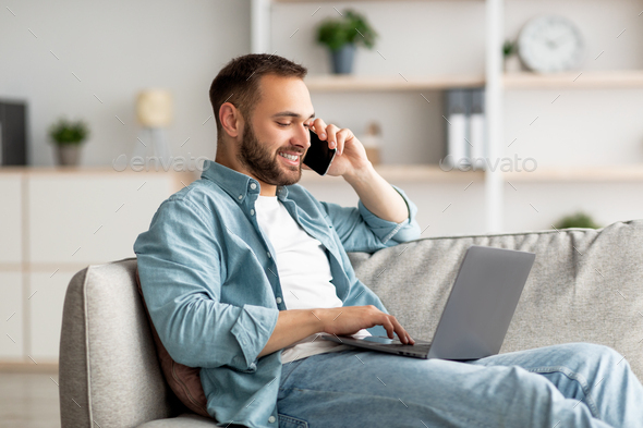 Attractive young guy talking on smartphone and using laptop computer on couch at home office - Stock Photo - Images