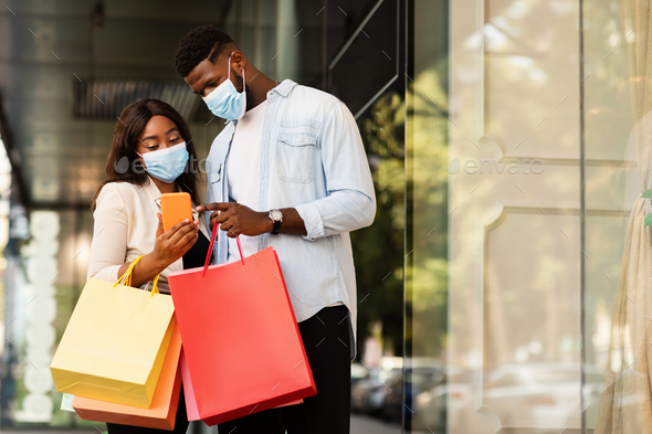 Portrait of black couple using cellphone wearing masks near mall - Stock Photo - Images