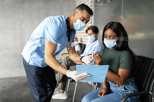 Black lady in face mask signing medical file before vaccination - Stock Photo - Images