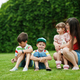 Young mother with three kids sitting in green grass at courtyard. - PhotoDune Item for Sale