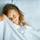 Little girl wakes up from sleep on a big and cozy bed white linen in the at home - PhotoDune Item for Sale
