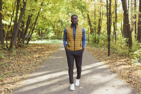 African american student walking in the park in autumn season - Stock Photo - Images
