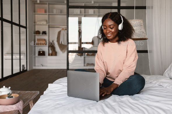 African Female Using Laptop Wearing Headphones Working Online At Home - Stock Photo - Images