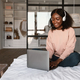 African Female Using Laptop Wearing Headphones Working Online At Home - PhotoDune Item for Sale