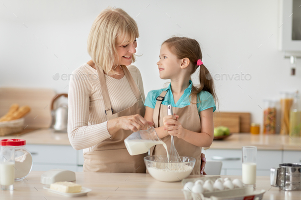 Happy mature lady and her granddaughter kneading dough - Stock Photo - Images