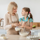 Happy mature lady and her granddaughter kneading dough - PhotoDune Item for Sale