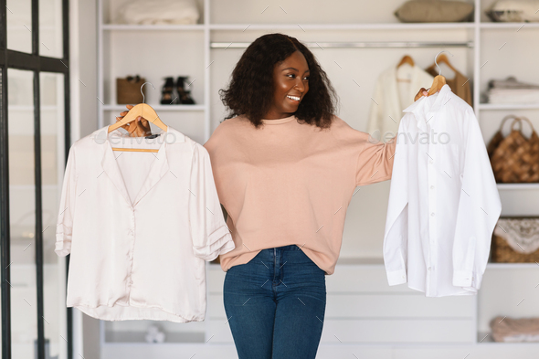 Happy African Woman Shopping And Choosing Clothes Holding Shirts Indoors - Stock Photo - Images
