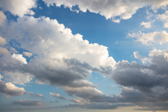 Fluffy cumulus clouds on blue sky background. Cloudscape white and grey color - Stock Photo - Images