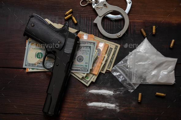 Drugs smuggling and trafficking, Handcuffs, pistol money and cocaine on wooden table background - Stock Photo - Images