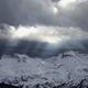 sunbeams through clouded sky over mountain peaks - PhotoDune Item for Sale