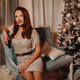 A girl in an evening dress is sitting on the sofa near the Christmas tree - PhotoDune Item for Sale