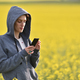 Young woman in hoodie texting a message on her smart phone - PhotoDune Item for Sale