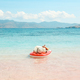 Sunbathing on inflatable mattress on the beach - PhotoDune Item for Sale