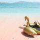 Woman on beach sitting on inflatbale swan - PhotoDune Item for Sale
