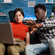 Married interracial couple looking at modern laptop - PhotoDune Item for Sale