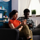 Interracial couple sitting on couch relaxing at home - PhotoDune Item for Sale