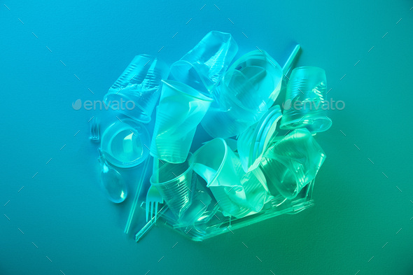top view of pile of crumpled plastic bags, cups, straws and forks with copy space in blue light - Stock Photo - Images