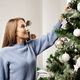 Young blonde woman on blue sweater decorating Christmas tree - PhotoDune Item for Sale