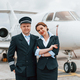Man with woman. Aircraft crew in work uniform is together outdoors near plane - PhotoDune Item for Sale