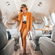 Uses phone. Young passenger woman in yellow clothes is flying in the plane - PhotoDune Item for Sale