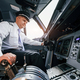 Pilot on the work in the passenger airplane. Preparing for takeoff - PhotoDune Item for Sale