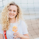 Adorable glad young woman has bushy curly hair, smiles gently, holds glass of orange cocktail - PhotoDune Item for Sale