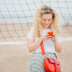 Pleasant looking blonde female holds cell phone, shares photos in social networks - PhotoDune Item for Sale